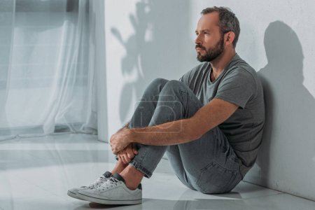 side view of sad bearded mid adult man sitting on floor and looking away