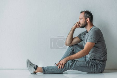 side view of frustrated bearded middle aged man sitting on floor and looking away