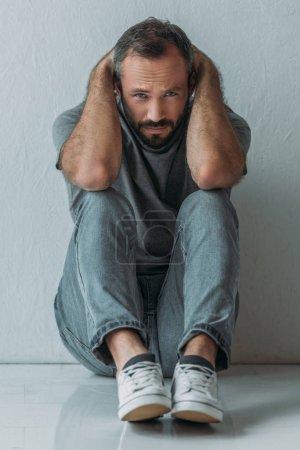 peur de l'homme déprimé assis sur le sol avec les mains derrière la tête et regarder la caméra
