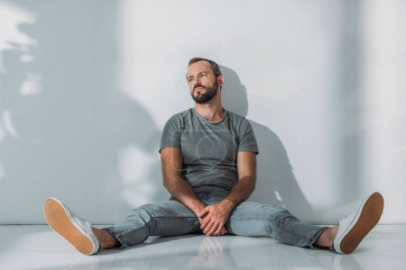 Photo for Full length view of depressive bearded middle aged man sitting on floor and looking away - Royalty Free Image