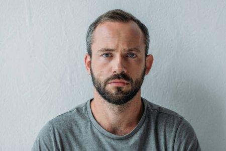 Portrait de malheureux homme barbu, regardant la caméra sur fond gris