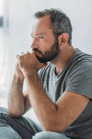 sad handsome bearded man sitting with hands on chin and looking away