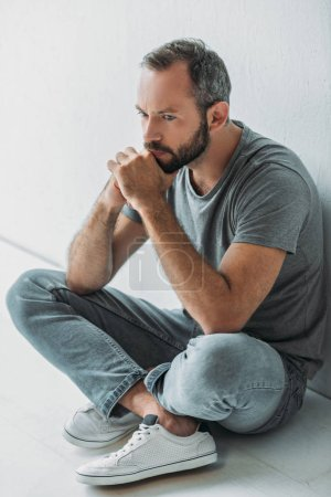 high angle view of sad bearded man sitting in floor and looking away