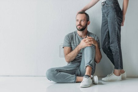 Photo for Cropped shot of young woman touching frustrated bearded man sitting on floor and looking away - Royalty Free Image