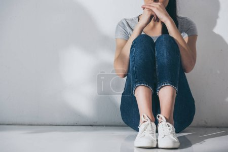Photo for Cropped shot of depressed young woman sitting on floor near grey wall - Royalty Free Image