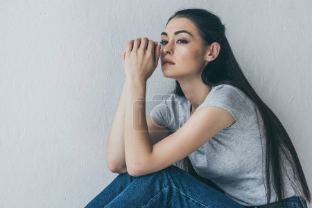 Photo for Upset young brunette woman sitting and looking away on grey - Royalty Free Image