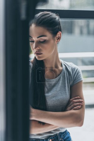 depressive young brunette woman standing with crossed arms near window