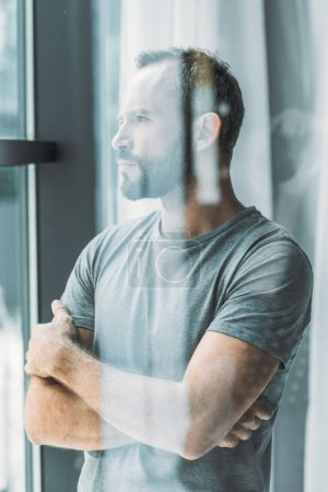 selective focus of bearded middle aged man standing with crossed arms and looking at window