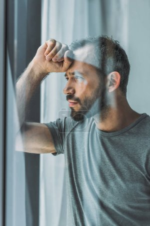 side view of sad bearded man looking at window