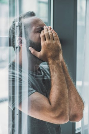 side view of depressed frustrated bearded man crying with hands on face