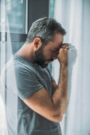side view of depressed frustrated bearded man standing near window