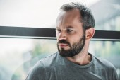 portrait of unhappy bearded man standing near window and looking away