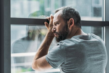 Photo for Upset bearded man leaning at window and looking through it - Royalty Free Image