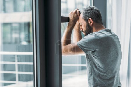Photo for Depressed bearded man leaning at window and looking through it - Royalty Free Image