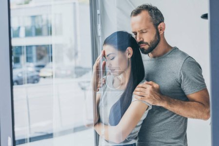bearded man supporting sad stressed woman with closed eyes standing near window