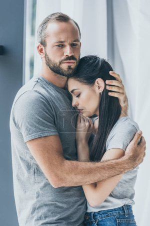 Photo for Upset bearded man hugging and supporting depressed young woman - Royalty Free Image