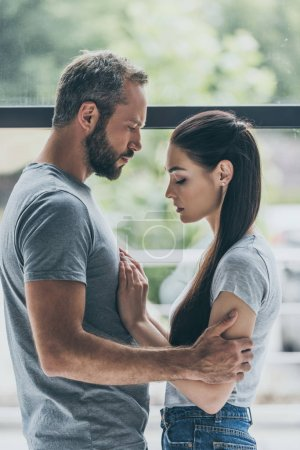 side view of bearded man embracing sad young girlfriend while standing together near window