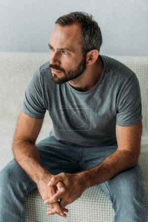 bearded thoughtful middle aged man sitting on couch and looking away