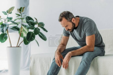 depressed bearded mid adult man sitting on couch and looking down