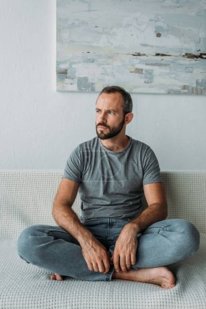 pensive bearded mid adult man sitting on couch and looking away
