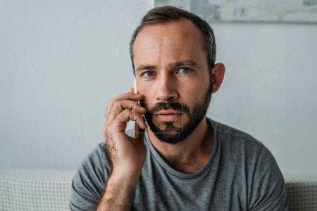 frustrated bearded man talking by smartphone and looking at camera