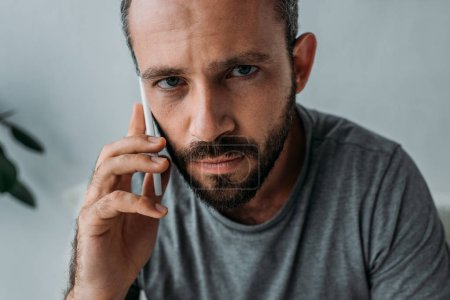 upset bearded man talking by smartphone and looking at camera