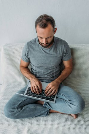 Photo for High angle view of unhappy bearded man sitting on couch and using laptop - Royalty Free Image