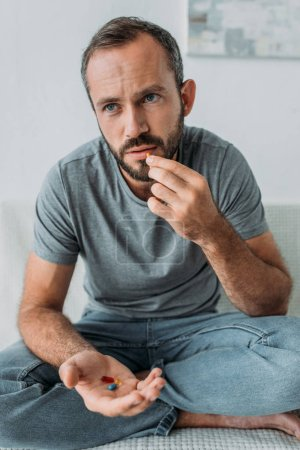 unhappy bearded man sitting on couch and taking pills