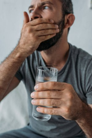close-up view of bearded mid adult man holding glass of water and taking medicine