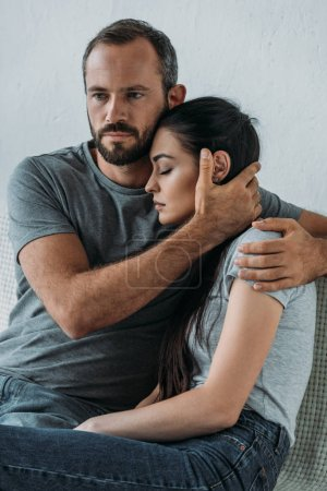 bearded man supporting and hugging stressed sad woman sitting on couch