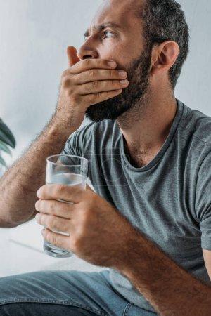 bearded man holding glass of water and taking medicine