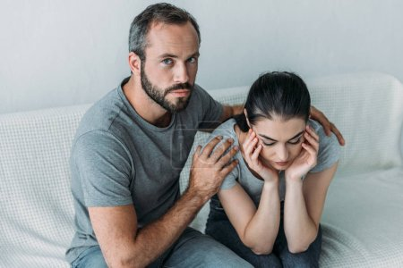 high angle view of bearded man supporting upset girlfriend and looking at camera