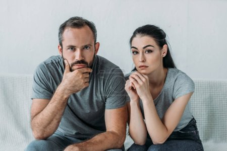 sad couple sitting on couch and looking at camera, relationship difficulties concept