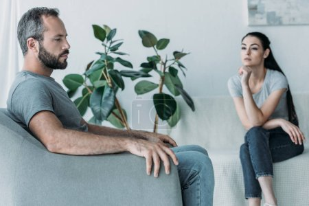 upset bearded man sitting on armchair and frustrated woman sitting on couch, relationship difficulties concept