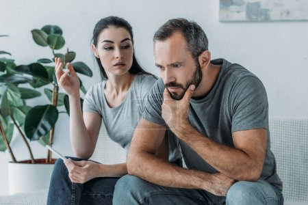 frustrated young woman holding pregnancy test and looking at upset partner