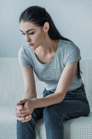 upset young brunette woman sitting on couch and looking down