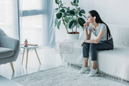 Photo for High angle view of sad young woman in depression sitting on couch and looking away at home - Royalty Free Image