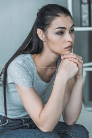 beautiful sad young woman in depression sitting and looking away at home