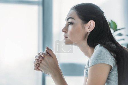 side view of beautiful upset brunette girl looking away