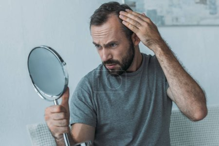 bearded middle aged man with alopecia looking at mirror, hair loss concept