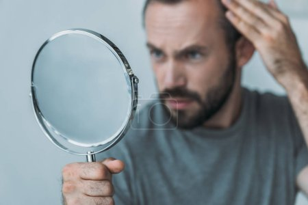 close-up view of bearded mid adult man with alopecia looking at mirror, hair loss concept