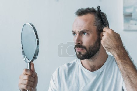 bearded middle aged man combing hair and looking at mirror, hair loss concept