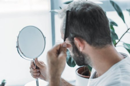 middle aged man combing hair and looking at mirror, hair loss concept