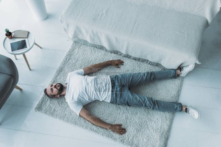Photo for Top view of sad bearded middle aged man with depression lying on carpet at home - Royalty Free Image