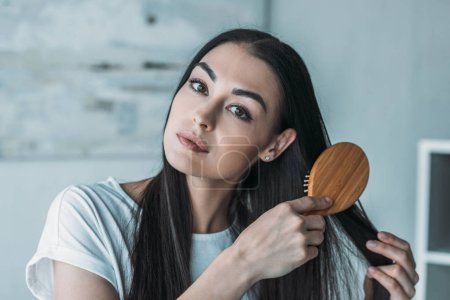 young brunette woman combing hair with hairbrush and looking at camera