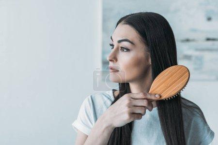 Photo pour Jeune femme brune peigner les cheveux avec une brosse à cheveux et détourner les yeux - image libre de droit