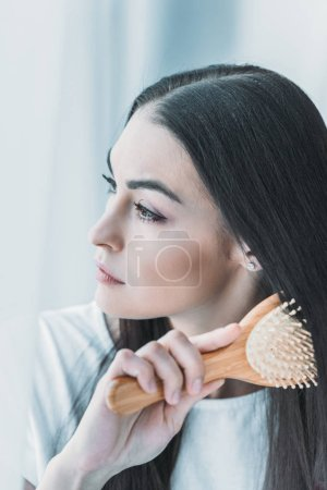 young pensive brunette woman combing hair with hairbrush and looking away