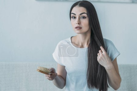 upset brunette woman holding hairbrush and looking at camera, hair loss concept