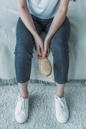cropped shot of young woman holding hairbrush and sitting on couch, hair loss concept