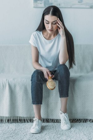 upset young woman holding hairbrush and sitting on couch, hair loss concept